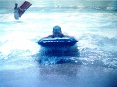 The author, Jim McGillis in 1960, riding an inflatable raft in the surf at Sorrento Beach, Santa Monica, California - Click for larger image (http://jamesmcgillis.com)