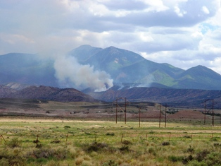 Wild fire burns laterally across a ridge near La Sal Mountains, and Spanish Valley, Utah.