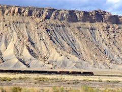 An eastbound train on the Union Pacific Railroad line near Crescent Junction and Brendel, Utah, with the Book Cliffs in the background - Click for larger image (http://jamesmcgillis.com)
