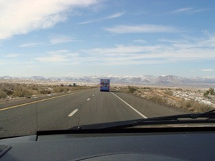 Harlem Globetrotters Tour Bus heads toward snowy mountains on I-40 east of Kingman, Arizona - Click for closeup image (http://jamesmcgillis.com)