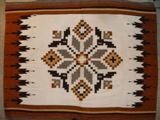 Close up of a hand loomed Navajo rug, with white background, corn motif and brown border - Click for larger image (http://jamesmcgillis.com)