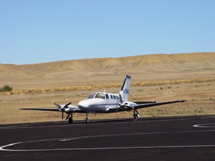 At Moab Airport, a twin-engine private plane shares the tarmac with  commercial aircraft, Canyonlands Field, Moab, Utah - Click for larger image (http://jamesmcgillis.com)