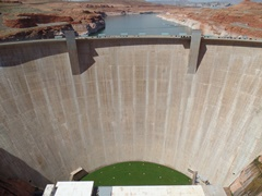 In this view of the front of Glen Canyon Dam, a patch of green in the lower-right indicates that seepage has worked around the dam and is exiting the canyon walls through a horizontal fissure or fault in the soft sandstone - Click for larger image (https://jamesmcgillis.com)
