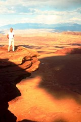 The author's father, Dr. L.N. McGillis tempting fate on a rocky outcropping at Dead Horse Point in 1965. Note the absence of settling ponds in the mid-ground at a place called Potash. The iconic blue ponds would not appear until 1970 - Click for larger image (http://jamesmcgillis.com)