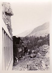 With a rock outcropping overhead, the Denver & Rio Grande Engine No. 478 rounds a curve at the summit of a climb on the was from Durango to Silverton in 1965 - Click for larger image (http://jamesmcgillis.com)