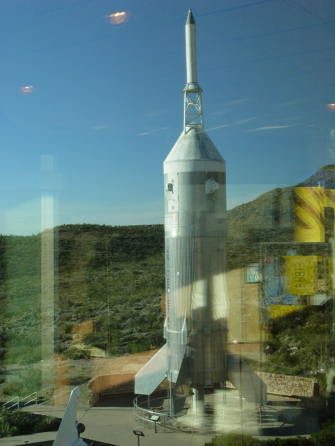 Reflected in a window, a test rocket appears to blast off from a static display, Museum of Space History, Alamogordo, New Mexico (http://jamesmcgillis.com)