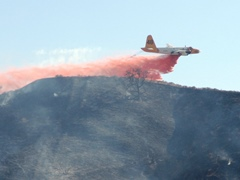 Lockheed P2V-7 Air Tanker Number 48 completes a low-level drop of fire retardant on a brush fire in Simi Valley, California - Click for larger image (http://jamesmcgillis.com)