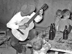 The inimitable and ineffable Ralph Newcomb, playing guitar at a UNM beer party in Albuquerque, New Mexico 1954 - Click for larger image (http://jamesmcgillis.com)