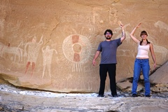 A young couple visiting the Sego Canyon Petroglyph Site mimics the pose of the ancient couple to the left, in this image - Click for larger image (https://jamesmcgillis.com)