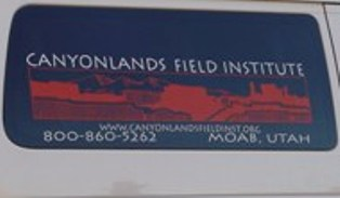 Canyonlands Field Institute logo sign on the window of a passenger van parked at Seven Mile Canyon, Moab, Utah - Click for larger Image (https://jamesmcgillis.com)