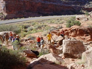 Led by author Craig Childs (center, wearing a brimmed hat), a group of budding authors views an ancient petroglyph site, on Utah Highway 313 at the entrance to Seven Mile Canyon - Click for larger image (https://jamesmcgillis.com)